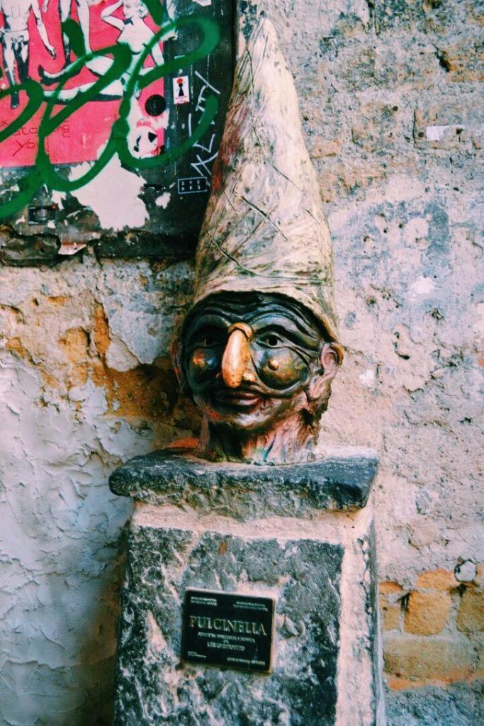 Bust of Puicinella in Naples. The statue head is on a pillar against a wall. Puicinella has a tall hat on and a black mask with a large nose.