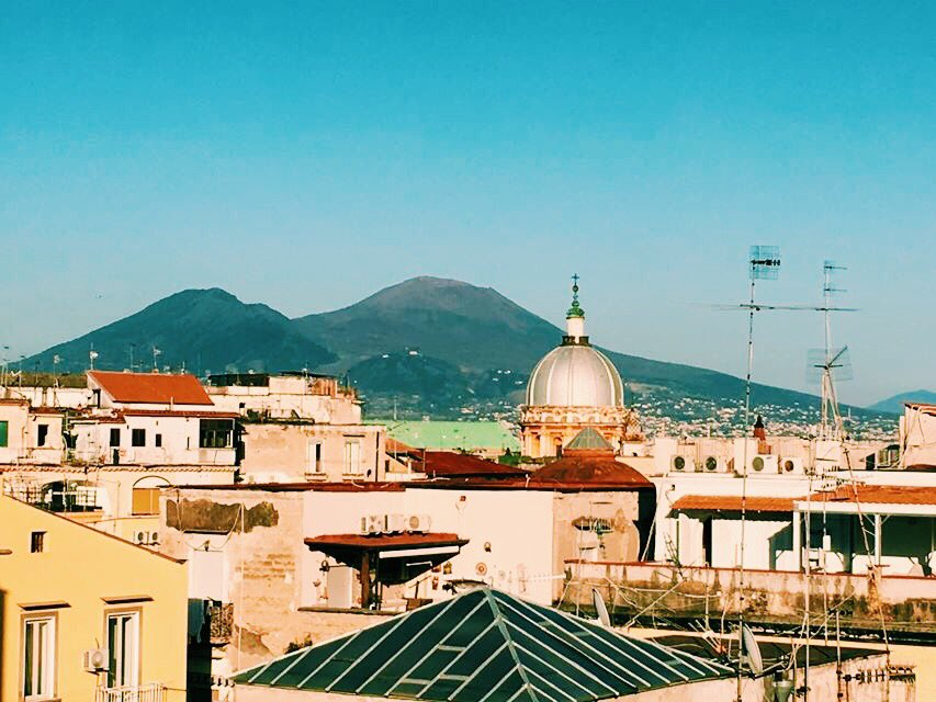 View from a roof top in Naples with buildings across the lower third and Vesuvius behind with a blue sky.