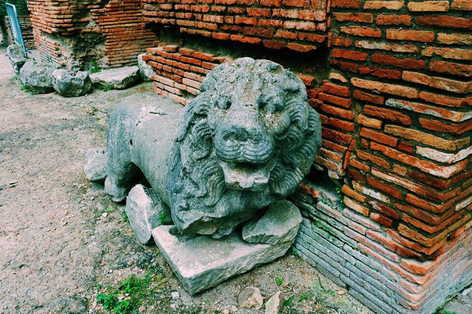 Lion statue at the Roman Theatre at Benevento. The lion has no front legs and is crumbling. It rests against a red brick wall.