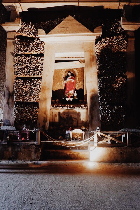 Dark image of a shrine to Jesus in the Cimitero Delle Fontanelle. A statue of Jesus is in the centre. Surrounding the statue are pillars of long bones piled onto each other. The shrine is roped off at the front.
