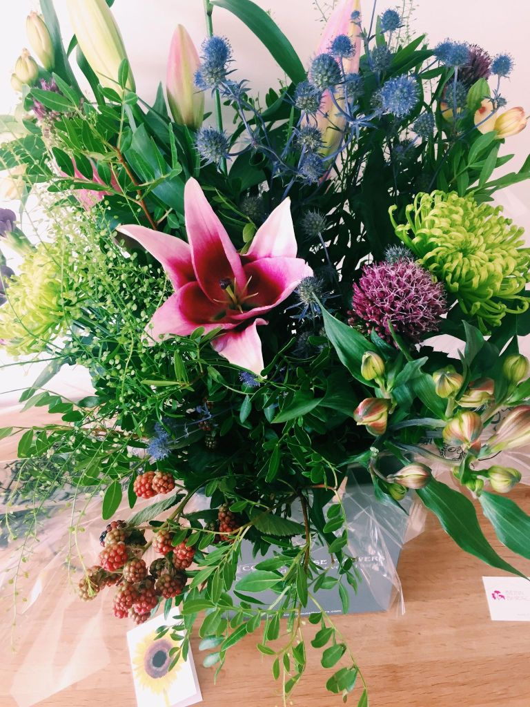 A large bunch of flowers with a purple Lily in the middle and lots of leaves and greenery
